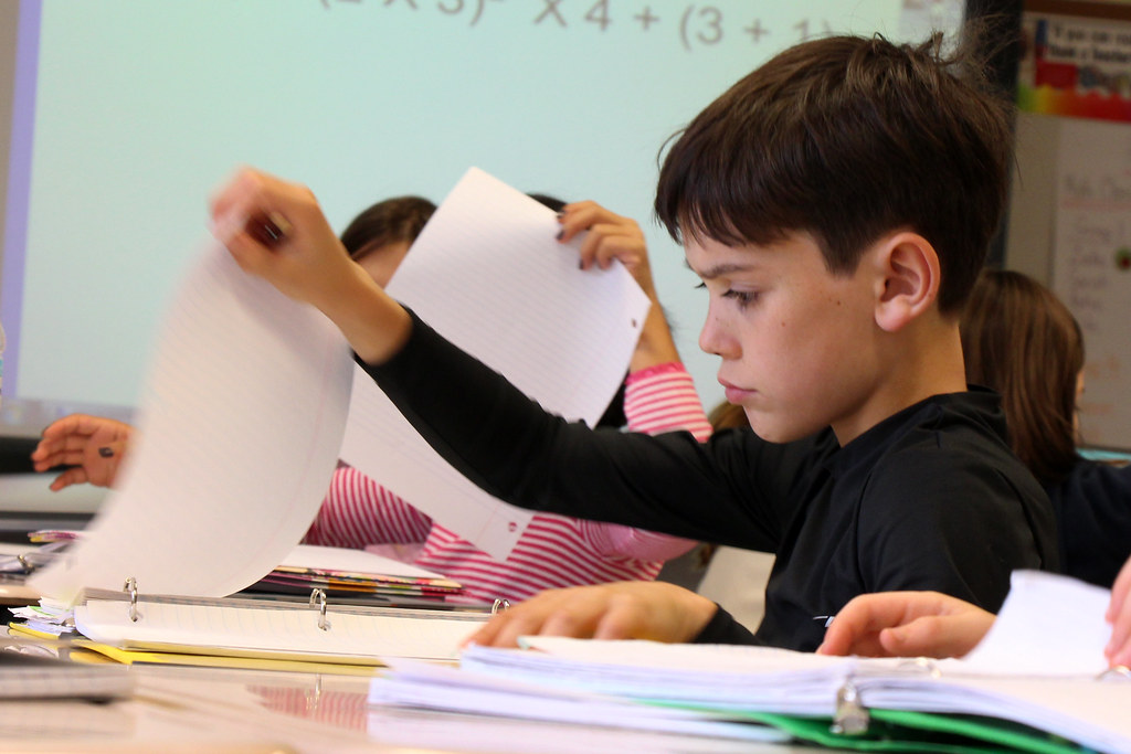 Young Boy with Executive Function Disorder Flipping Through Papers in Three-Ring Binder at School